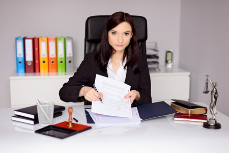 certifying: Brunette woman Notary Public indicates the place for signature on notary act . Law office concept.