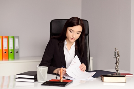 certifying: Brunette woman Notary Public reading and signing testament . Law office concept.