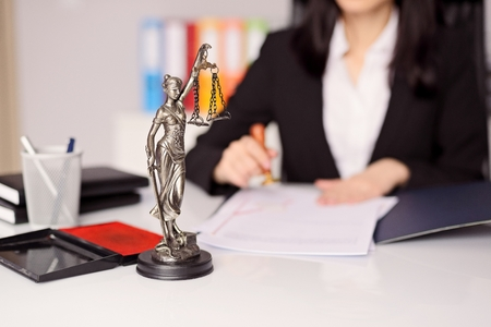 Statuette of Themis - the goddess of justice on lawyers desk. Lawyer is stamping the document. Law office concept. Stock Photo