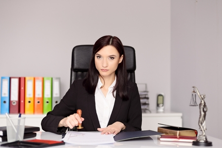 certifying: Brunette woman Notary Public stamping notary act . Law office concept.