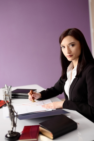 signing authority: Brunette woman Notary Public notarizes the power of attorney. Law office concept.