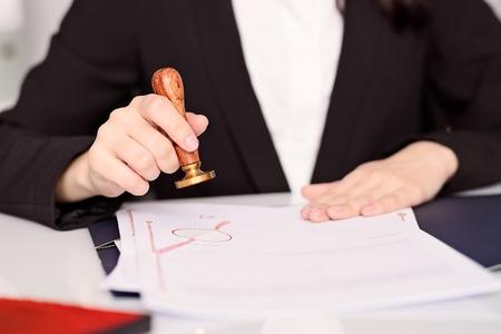 Primo piano su notai e donna pubblica mani stampaggio atto notarile. concetto di ufficio legge.