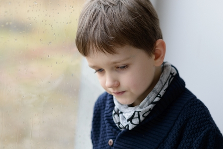 Pensive 7 year old boy standing by the window. Rainy day.