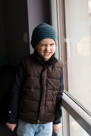 conflicted: Offended little boy standing by the window. He is wearing a brown vest and striped cap. Stock Photo