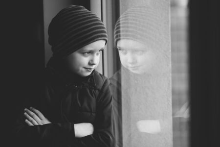 7 year old: Confident 7 year old boy looks out the window. He is wearing a brown vest and striped cap. black and white Stock Photo