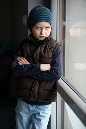 agression: Offended 7 year old boy standing by the window. He is wearing a brown vest and striped cap. Stock Photo