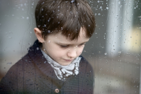 7 year old: Sad depressed 7 year old boy standing by the window. Rainy day. Selective focus.