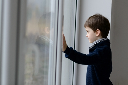 7 year old: Thoughtful 7 year old boy standing by the window. Rainy day.