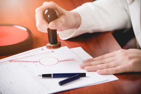 certifying: Woman Notary Public stamping the contract. Law office. Stock Photo
