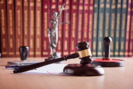 Court Judge's gavel, Themis - the goddess of justice, notary public stamper and law codes in the background. Law office. Law concept.