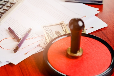 signing authority: Money under the notary public stamper. Bribe, corruption concept. Stock Photo