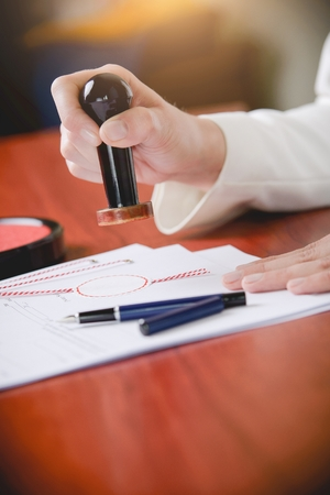 certifying: Woman Notary Public stamping the document. Law office. Stock Photo