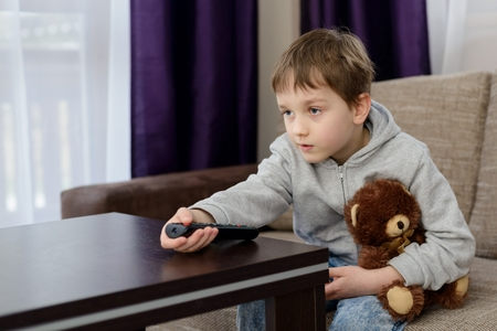 changing channels: 7 year old boy child sitting on the sofa and watching tv. Hugs his favorite teddy bear and changing channels by remote control. Stock Photo