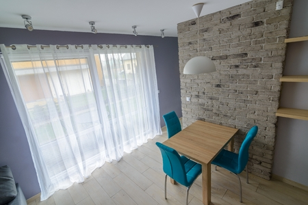 Dining Room With Old Grey Brick Wall, Wooden Table, Turquoise