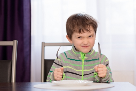 7 years old: Annoyed hungry 7 years old boy holding fork and knife and waiting for dinner