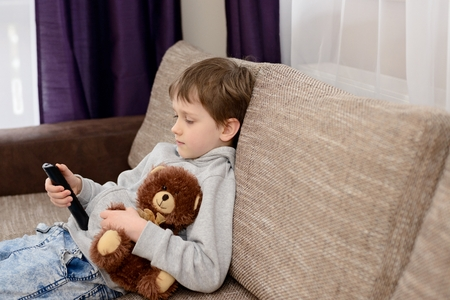 cute teddy bear: Bored 7 year old boy child sitting on the sofa and watching tv. Hugs his favorite teddy bear and changing channels by remote control.
