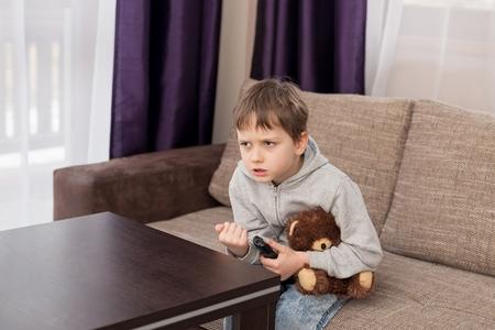nerveux: Nervous 7 ans enfant garçon assis sur le canapé et regarder la télévision. Étreintes son ours en peluche préférée et l'évolution des canaux par télécommande.