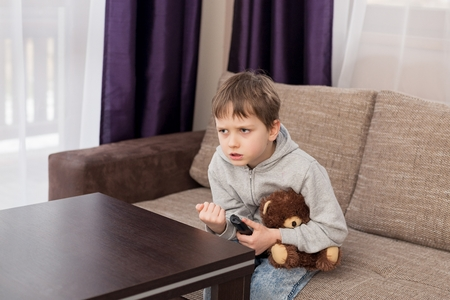 7 year old: Nervous 7 year old boy child sitting on the sofa and watching tv. Hugs his favorite teddy bear and changing channels by remote control. Stock Photo