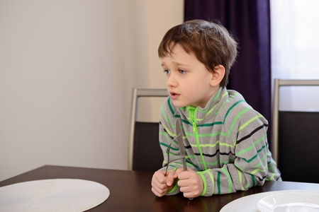 a little dinner: Little 7 years old boy holding fork and knife and waiting for dinner