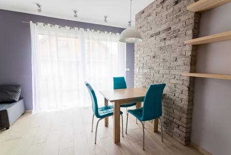 dining table and chairs: Modern dining room with old grey brick wall, wooden table, turquoise leather chairs and empty shelves. Grey spotlight on ceiling. Stock Photo