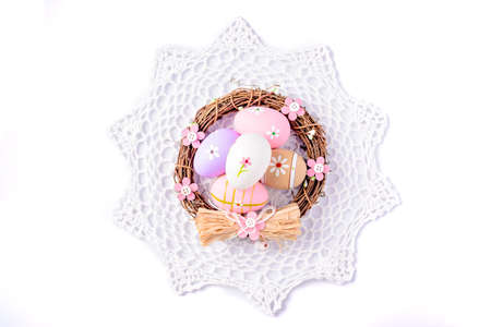 serviette: Easter eggs painted in pastel colors in the nest on white serviette . Easter concept