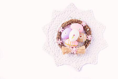 servilleta de papel: Huevos de Pascua pintados en colores pastel en el nido en la servilleta blanca. concepto de Pascua