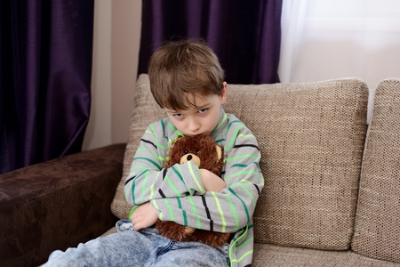 alone person: Sad boy hugs his favorite teddy bear and sitting on the sofa in the living room Stock Photo