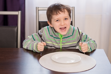 dinnertime: Happy smiling boy child waiting for dinner. Holding fork and knife in his hands Stock Photo