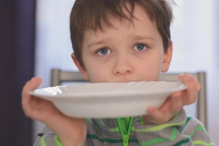 Chłopiec głodna o pięknych oczach czekając na kolację. Trzymając pusty talerz w dłoniach
