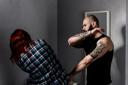 adult rape: Muscular man beating his redhead wife. Domestic violence