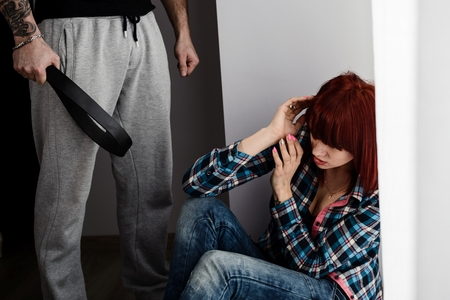 woman sitting on the floor scared of a husband. Woman is victim of domestic violence and abuse.
