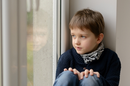 fantasize: Thoughtful little boy sitting on the windowsill and looking through the window. Rainy day