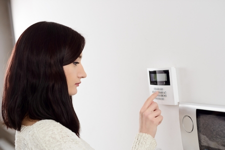 若いブルネットの女性はホームセキュリ ティー警報のキーパッドにコードを入力します。アラーム キーパッドの横にあるインターホン。