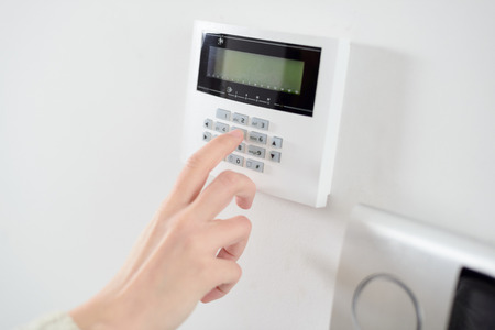 Close up on brunette womans hand entering code on keypad of home security alarm. Video intercom next to alarm keypad. Stock Photo