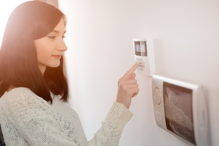 Young brunette woman entering code on keypad of home security alarm. Video intercom next to alarm keypad. Banco de Imagens - 53756504