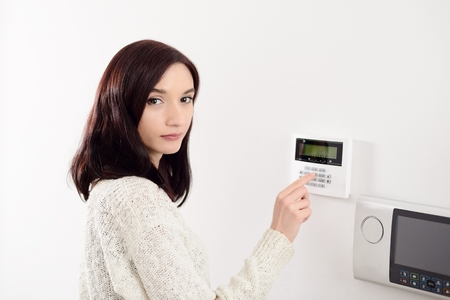 home security alarm: Young brunette woman entering code on keypad of home security alarm. Video intercom next to alarm keypad.
