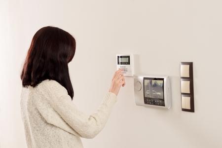 Jeune femme brune entrant le code sur le clavier de l'alarme de sécurité à domicile. Interphone vidéo suivante au clavier d'alarme.