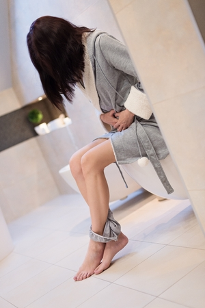 Brunette woman sitting on toilet in the bathroom. She is holding her stomach. Wears a grey dressing-gown