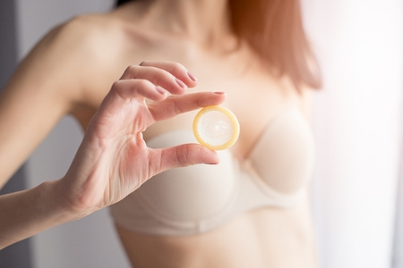 safe sex: Woman in underwear is holding a condom for a safe sex. Safe sex concept Stock Photo