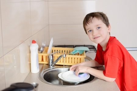 7 year old: smiling 7 year old boy washes dishes in the kitchen. Dressed in a red t-shirt