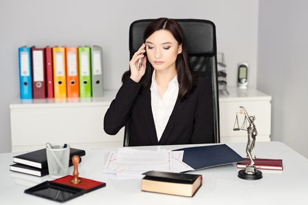 notary: Brunette woman - Notary Public talking on cellphone in her office