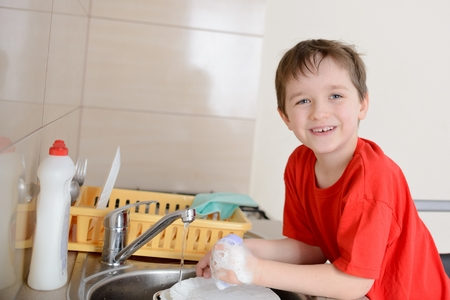 7 year old: 7 year old boy washes dishes in the kitchen. Dressed in a red t-shirt