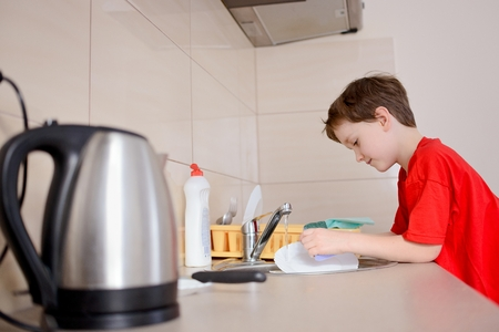 7 year old: Happy, smiling 7 year old boy washes dishes in the kitchen. Dressed in a red t-shirt