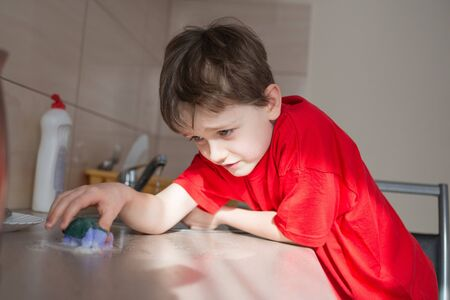 7 year old: Satisfied 7 year old boy cleans cabinets in the kitchen. Dressed in a red t-shirt Stock Photo