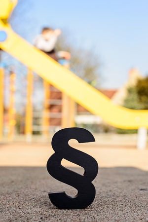 family law: Black paragraph symbol on children playground. Family law or playground accident concept. Stock Photo