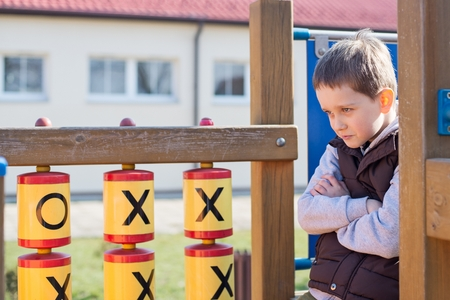 outcast: Offended boy on the playground in the school Stock Photo