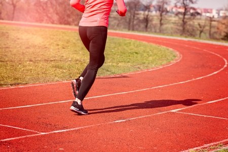 spring training: Legs of a woman running around the track on a sunny spring day. Woman running concept. Runner jogging training workout Stock Photo