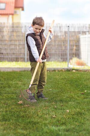 Little boy helping in the garden. Rakes the grass. Spring gardening Stock Photo