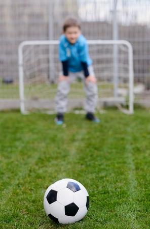 portero de futbol: pelota de f�tbol en el c�sped y f�tbol poco portero ahorro de la meta. f�tbol de juego infantil