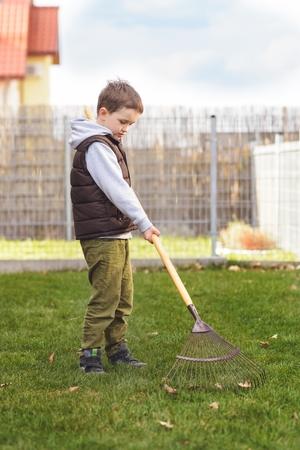 Child Helping In The Garden. Rakes The Grass. Spring Gardening Stock Photo    54674912